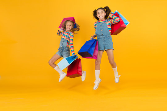 Online shop. happy shopaholic children. little girls care packages. free jump. Summer shopping. Buyer consumer concept. Holiday purchase saving. small kids with heavy shopping bags. big sale presents