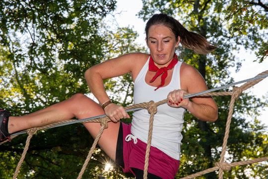 pretty sporty woman in obstacle Course rope ladder in Outdoor Boot Camp