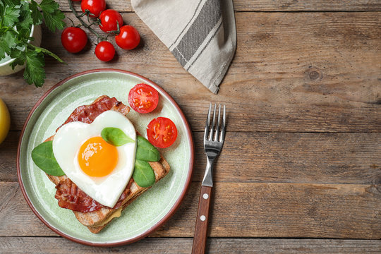 Tasty sandwich with heart shaped fried egg and bacon on wooden table, flat lay. Space for text