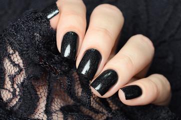 Foto auf Leinwand Maniküre dark blue manicure on a background of black lace