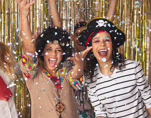 Foto op Canvas Carnaval Women dressed as Pirate and Hippie at Brazilian Carnival. Brazilian Carnival. Young women in costume enjoying the carnival party throwing confetti. .