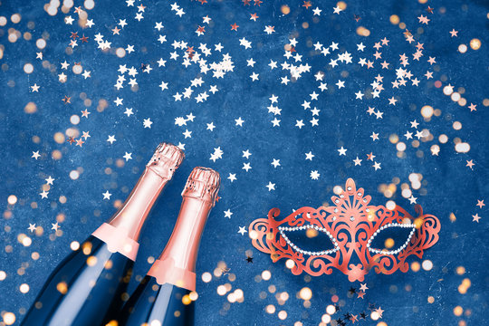 Two champagne bottles, carnival mask and confetti stars on blue background. Flat lay of Christmas, New Year, Purim, Carnival celebration concept.
