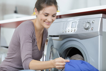 young female taking clothes out of washing machine