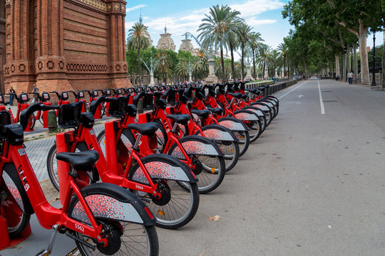 Barcelona, Spain - July 9, 2019: Bright red bicycles available for rent parked in a row at Passeig de Lluis Companys. Concept of environmentally sustainable transport. Bike rental service Bicing.