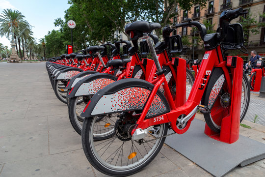 Barcelona, Spain - July 9, 2019: Red bicycles available for rent parked in a row at Passeig de Lluis Companys. Concept of environmentally sustainable transport. Bike rental service Bicing. Close up.