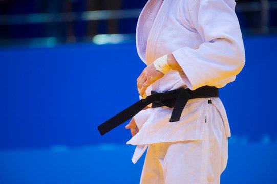 Judo fighter poses in white kimono with black belt. Japanese judo and jiu jitsu