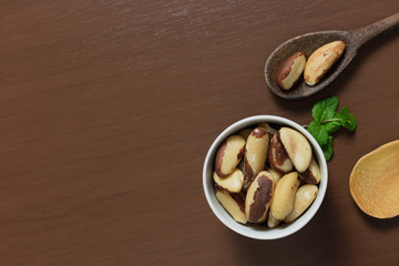 Brazilian nuts in a bowl on a wooden table. Kitchen background.