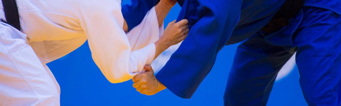 Two judo fighters in white and blue uniform. Martial arts competition - sambo, judo, karate, jiu jitsu, wrestling