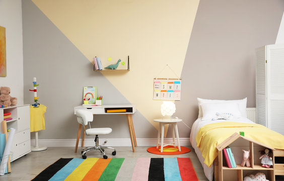 Stylish child room interior with comfortable bed and desk