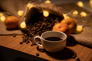 Poster Cafe Magical still life with a cup of brewed coffee, coffee grains and tangerines. Comfort and tranquility. Horizontal photo
