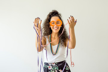 Foto op Canvas Carnaval Young woman smiling wearing carnival glasses and necklaces on white background