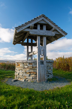 A rock wishing well with a wooden roof in a green field with blue sky and clouds.