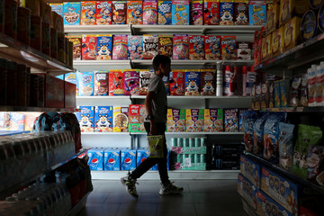 "A children passes in front of a shelf with cereal boxes at a ""bodegon"" named ""Mini Walmart"" in Puerto Cabello"