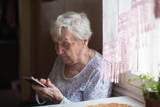 Old woman sits with a smartphone in her hands on the room.