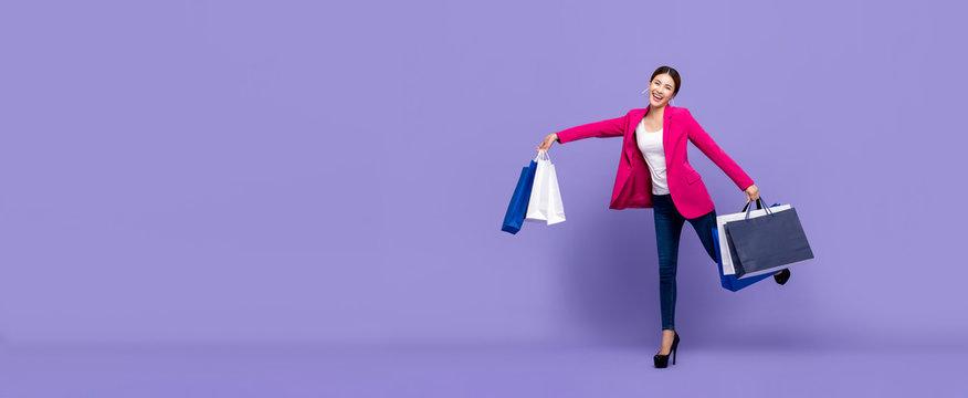 Smiling beautiful young Asian woman holding shopping bags
