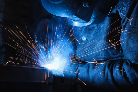 factory welder welds parts with a semi-automatic welding machine