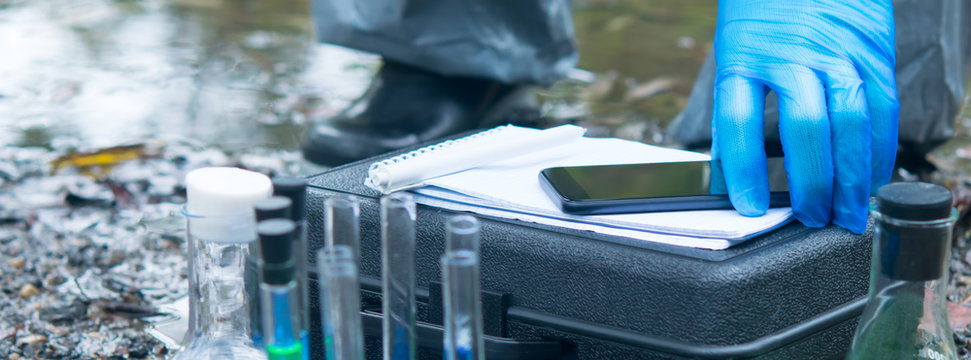 close-up of a scientist's hand in blue protective gloves, against the background of a river and test tubes with liquids, puts a mobile phone on a black suitcase for inventory