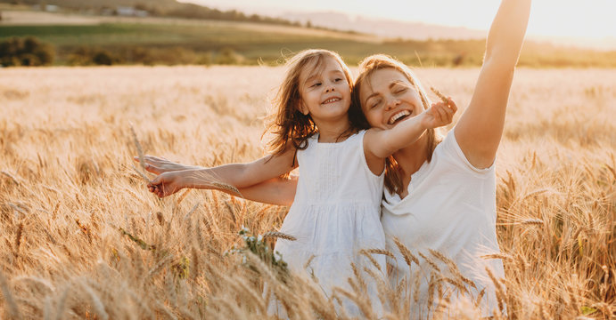 Portrait of a happy young mother and her lovely daughter playing and laughing in a field of wheat . Freedom concept.