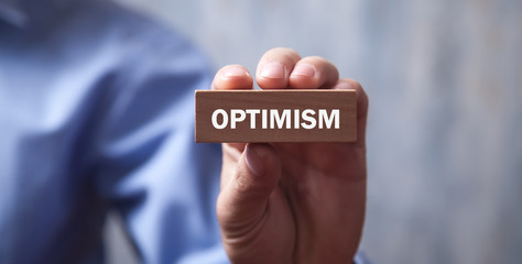 Wall Mural - Businessman holding Optimism text on wooden block.