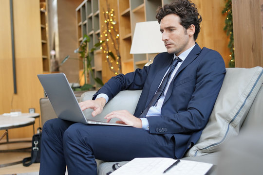 Businessman connected on laptop in hotel lounge