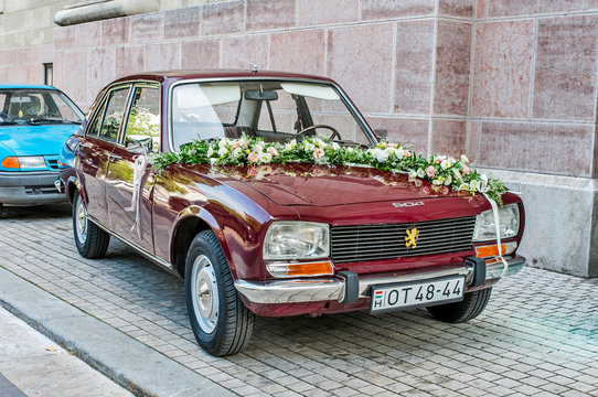 Closeup of wedding car Peugeot 504 with flowers