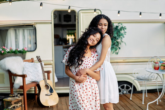 Two best friends embracing outdoors. Asian and afro american woman hugging and have great time together