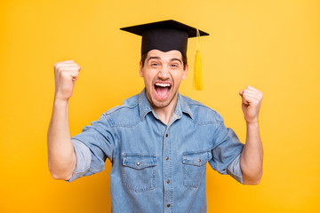 Photo of trendy stylish cheerful man rejoicing in graduating from university screaming making fists shouting isolated vivid color yellow background