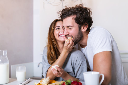 Beautiful young couple is feeding each other and smiling while cooking in kitchen at home. Happy sporty couple is preparing healthy food on light kitchen. Healthy food concept.