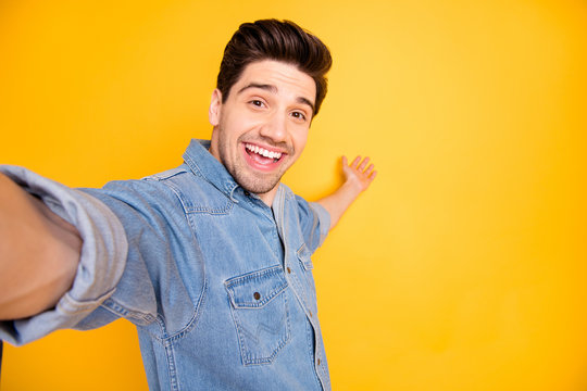 Photo of cheerful positive attractive man welcoming you to come to empty space behind him taking selfie isolated vivid color background
