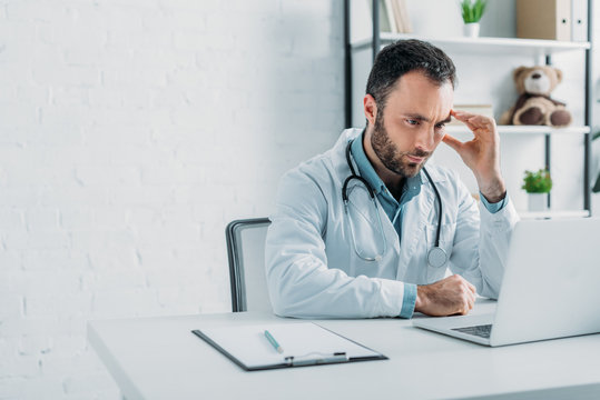 thoughtful doctor looking at laptop while sitting at workplace