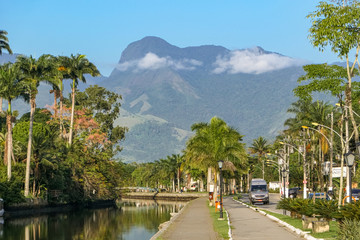 View from promenade with trees of river Perequê-Açu to the majestic Atlantic forest mountains in background, Paraty, Brazil