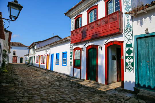 Typical cobblestone street with decorative and colorful colonial buildings in late afternoon light in historic town Paraty, Brazil
