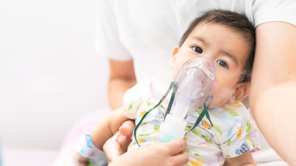 Close up of asian little baby boy is treated respiratory problem with vapor nebulizer to relief cough symptom in the hospital room , concept of pediatric patient care for sick in the hospital.