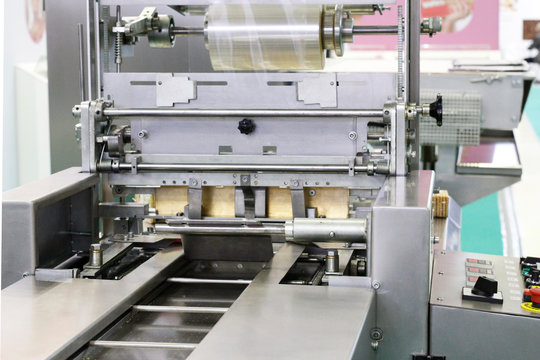Automatic packing machine. Filling equipment. Packing in a transparent cellophane film. Designing machines for the food industry.