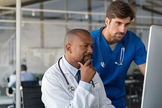 Doctor consulting patient medical record with nurse