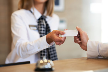 Receptionist giving key card to businesswoman at hotel front desk Wall mural