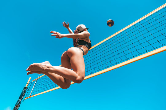 The ecstatic young girl in high flying with a ball. Jump up of sports young woman playing volleyball on sea beach against the blue sky. concept of a healthy lifestyle. Blocking the ball.