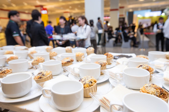 Group of empty coffee cups with snack cake on plate. Many rows of white cup for service hot tea or coffee in buffet and seminar event over Blurred people crowd backgrounds, shallow dof or more blur