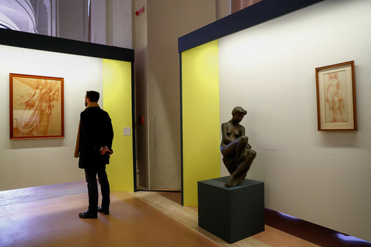 A visitor looks at an artwork during an exhibition of delicate works on paper at the Vatican