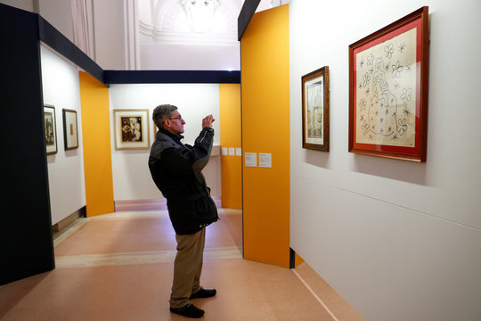 """A visitor takes a picture of the litograph on paper """"Virgin and Child on a background of flowers and stars"""" by Henri Matisse, during an exhibition of delicate works on paper at the Vatican"""