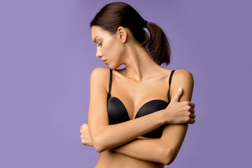 side view on beautiful female wearing black brassiere isolated over purple background, woman look down through shoulder