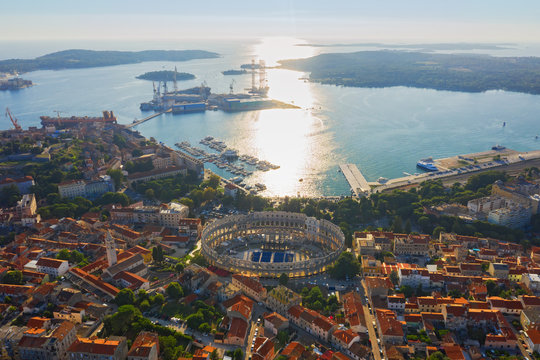 Aerial view of Pula in Croatia with Roman Amphitheatre, marina and port at sunset. Istria, Europe