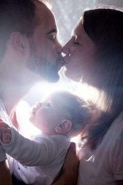 Eltern küssen sich beim Familie Fotoshooting