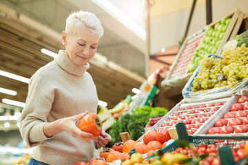 Keuken foto achterwand Keuken Waist up portrait of beautiful adult woman choosing fresh vegetables while grocery shopping at farmers market, copy space