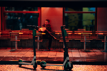 man alone sitting at the empty terrace of a cafe by night choosing for something to order