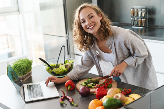 Happy young woman making a salad at the kitchen