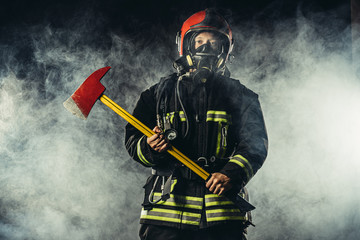 portrait of professional and confident fireman holding hammer, wearing protective uniform and helmet on head, stand isolated in smoky background