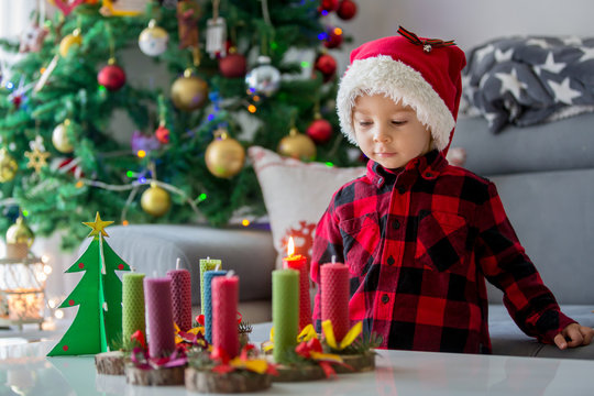 Close portrait of beautiful toddler blond boy, lighting beeswax candles