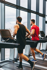 Two young man running on treadmill at gym