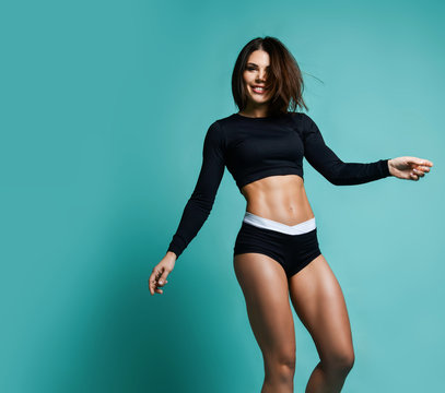 Fitness and diet concept. Portrait of young sporty happy woman with perfect body and beautiful abs is walking dancing